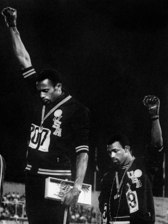 Jogos Olímpicos da Cidade do México, 1968: atletismo: os atletas negros norte-americanos Tommie Smith (centro) e John Carlos (dir.), medalhas de ouro e de bronze nos 200 m, fazem a saudação com o punho cerrado do grupo Panteras Negras, como protesto a conflitos raciais nos EUA