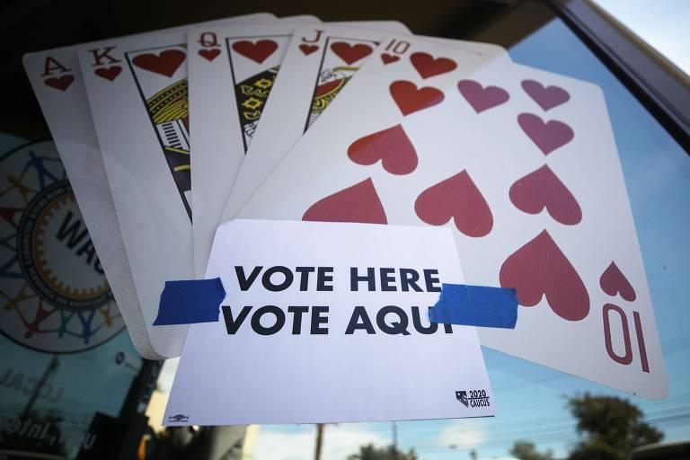 papel sulfite com texto 'vote here vote aqui' é colado numa vitrine com imensas cartas de baralho