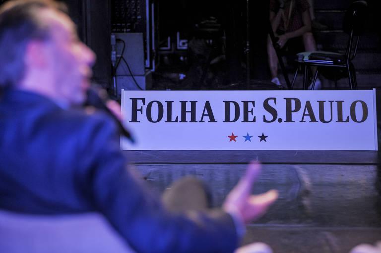 Roberto está no palco falando ao microfone, mas está fora de foco. Em destaque, o logo da Folha de S. Paulo