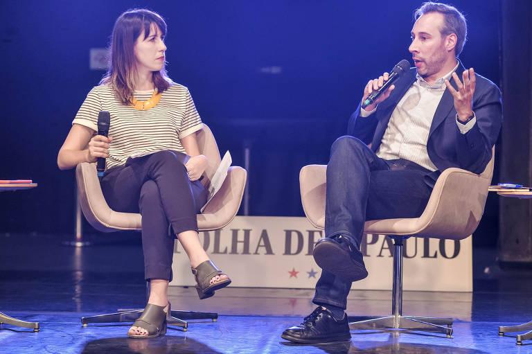 Roberto está de terno e gesticula com uma mão enquanto fala ao microfone. Flávia está de pernas cruzadas olhando para o colega enquanto ele fala.