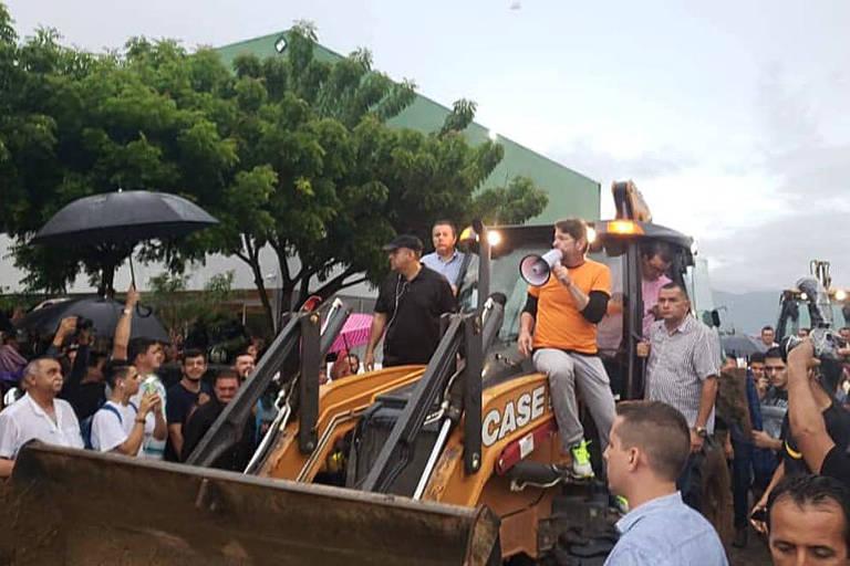 Cid Gomes aparece em cima de uma retroescavadeira com um megafone na mão; há uma multidão em volta