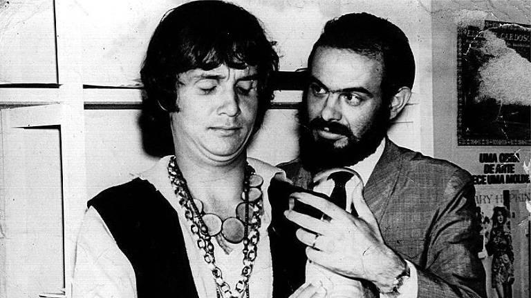 Roberto Carlos jovem, de colar, ao lado de Zé do Caixão de terno
