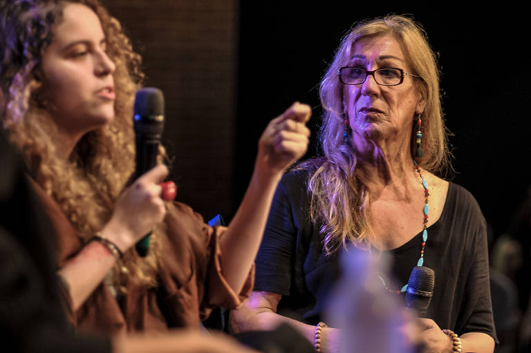 Estela May fala ao microfone e gesticula com uma mão enquanto Laerte a observa