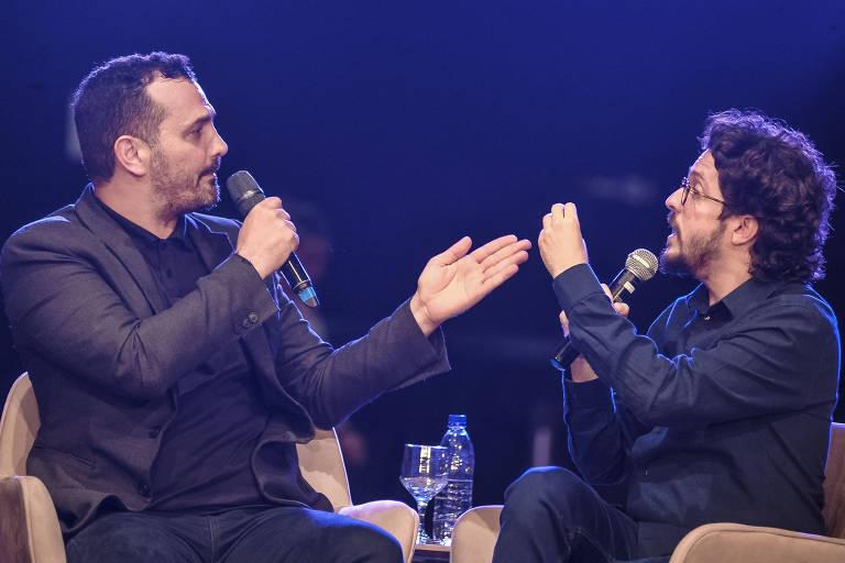 Os dois homens estão falando ao microfone e gesticulando um em direção ao outro enquanto se encaram