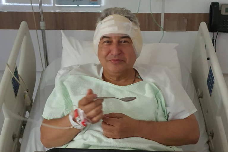 Ministro com orelhas protegidas comendo uma sopa em uma cama de hospital