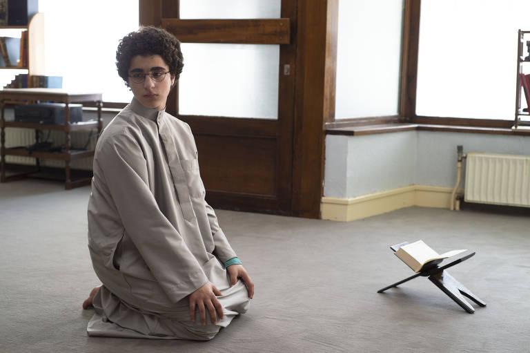 menino performa ritual de reza islâmico
