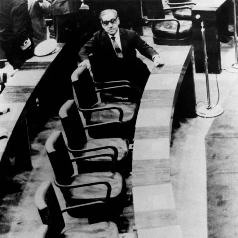 O marechal está de terno e óculos escuros sentado sozinho no plenário