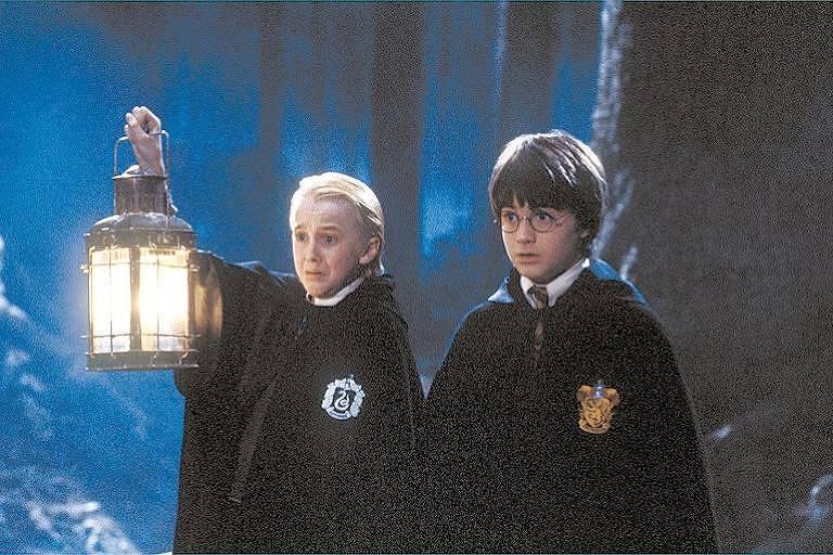 """Draco Malfoy (Tom Felton), à esquerda, segurando uma lanterna, e Harry Potter (Daniel Radcliffe) no filme """"Harry Potter e a Pedra Filosofal"""", adaptação cinematográfica do livro homônimo de J.K. Rowling"""