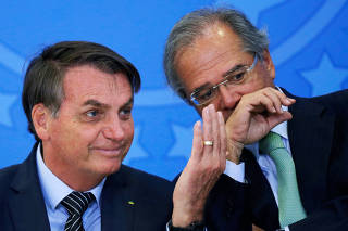 Brazil's President Jair Bolsonaro gestures next to Brazil's Economy Minister Paulo Guedes during a launch ceremony of real estate credit incentive program of the Caixa Economica Federal Bank at the Planalto Palace in Brasilia