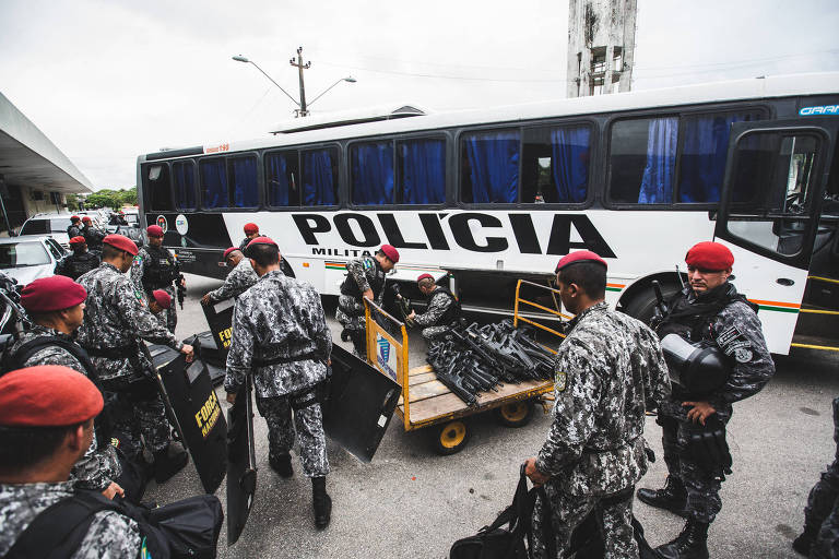 """Agentes uniformizados recolhem suas bagagens; aos fundo há um ônibus em que está escrito """"polícia"""""""