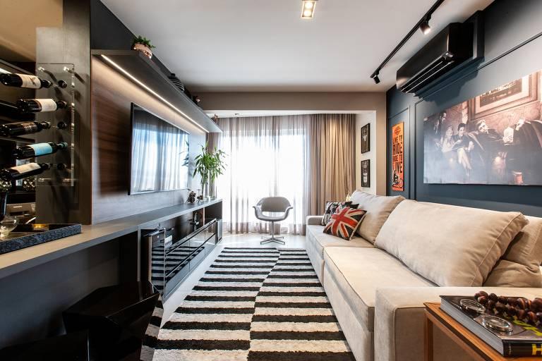 O apartamento em Alphaville de um homem solteiro levou decoração em estilo moderno. A paleta de cores é de tons neutros frios, como o cinza e o preto, e o toque de madeira traz contraste e aquece o ambiente.  O sofá é em suede liso e tom neutro, já o tapete ostenta estampa geométrica