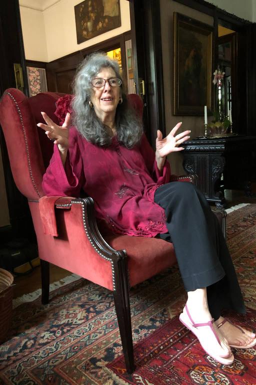 Cecilia Alves Pinto, 80 (completa 81 em maio de 2020), durante entrevista, em sua casa no bairro Pacaembu. Ela é uma senhora magra sentada em uma poltrona em sua sala de estar, embaixo dela há um sofá persa com cores quentes. Ela tem cabelo longo, abaixo dos ombros, grisalho (cinza escuro) e usa óculos.