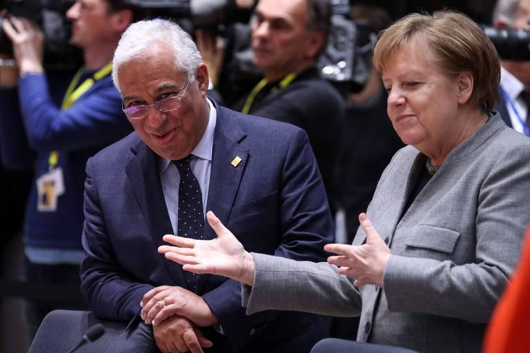 Merkel gesticula com as duas mãos, sentada ao lado de Costa