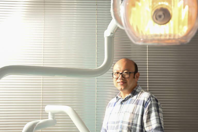 Homem com camisa listrada sorri para câmera, com cadeira de dentista aparecendo na imagem