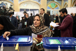 Woman casts her vote during parliamentary elections at a polling station in Tehran