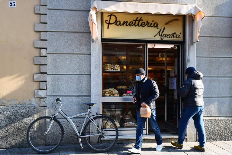 Homem vestindo máscara respiratória deixa uma padaria