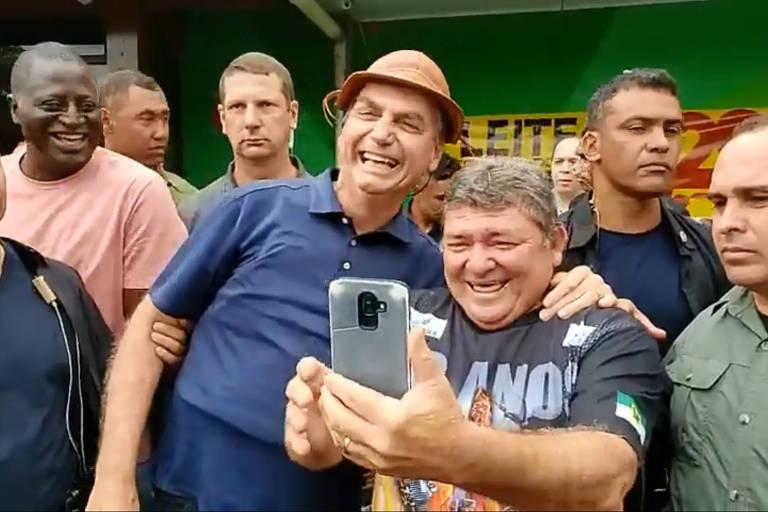 O presidente, vestindo um chapéu de vaqueiro nordestino, sorri para apoiadores ao lado de um homem que sorri e tira uma selfie