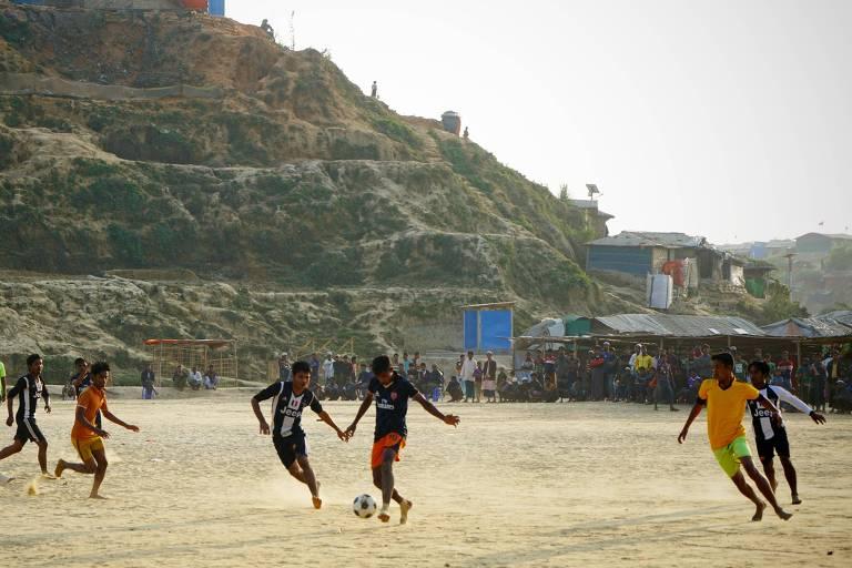 Homens de origem rohingya jogam futebol em campo de refugiados em Bangladesh