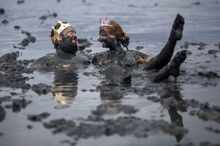 Casal, que usa uma espécie de coroa na cabeça, está mergulhado em lama escura