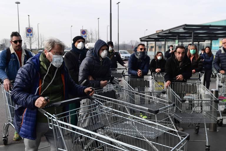 Moradores aguardam neste domingo (23) para poderem fazer compras; as liberações acontecem em pequenos grupos, de 40 pessoas, por vez