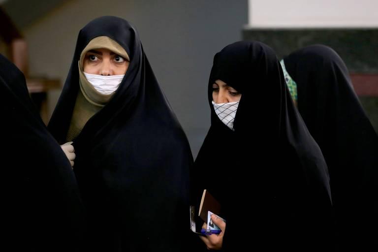 Em Teerã, iranianas com máscaras devido ao temos do coronavírus aguardam antes de depositar seus votos para as eleições parlamentares