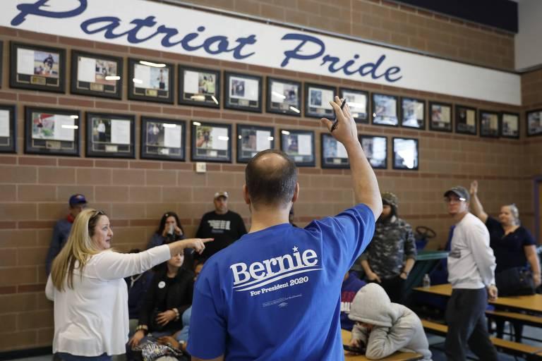 Apoiadores do senador Bernie Sanders levantam os braços para indicar preferência durante caucus em Nevada