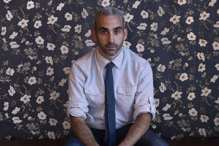 homem de cabelos brancos posa diante de papel de parede de florzinhas