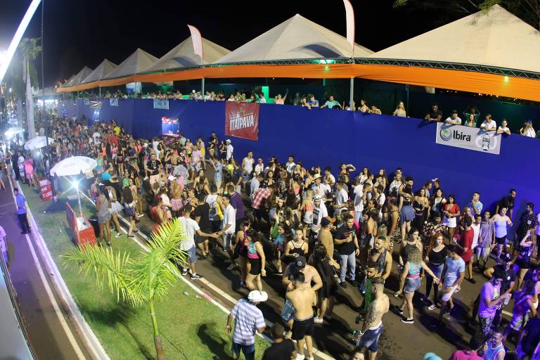Grupo de pessoas se locomove ao lado de tendas laranjas