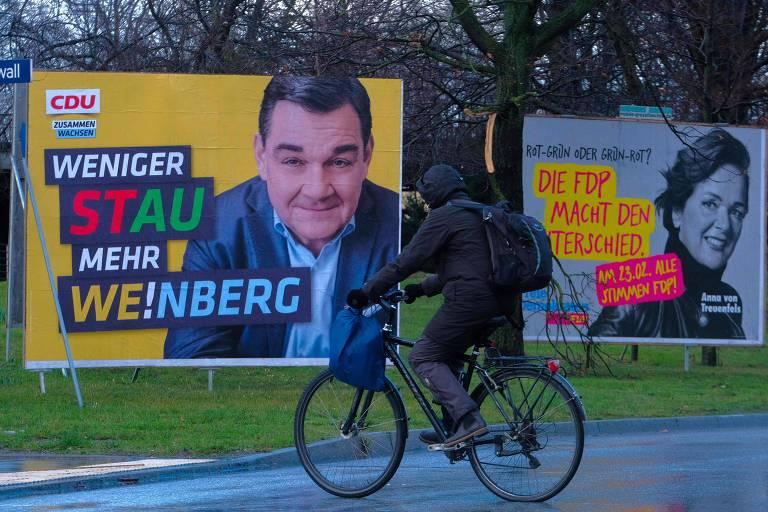 Ciclista passa por cartazes de campanha eleitoral em Hamburgo