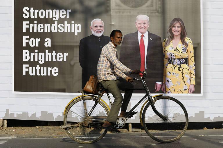 Cicilista passa em frente a outdoor com imagem de Narendra Modi, Donald e Melania Trump em Ahmedabad, na Índia,