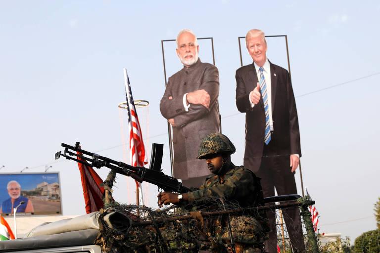 Soldado passa perto de bonecos de Narendra Modi e Donald Trump em Ahmedabad, na Índia