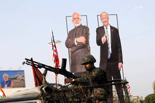 An Indian army soldier sits atop an armoured vehicle next to cutouts of India's Prime Minister Narendra Modi and U.S. President Donald Trump along a road, ahead of Trump's visit, in Ahmedabad