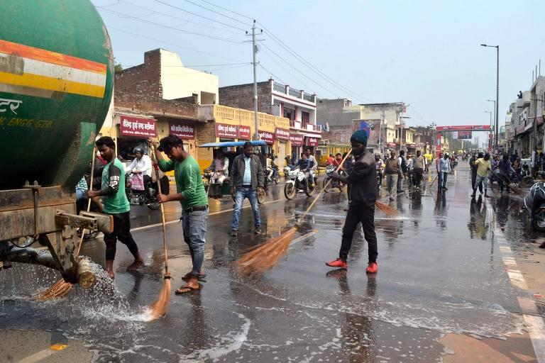 Trabalhadores lavam asfalto perto do aeroporto em Agra, em preparação para a visita de Trump à Índia