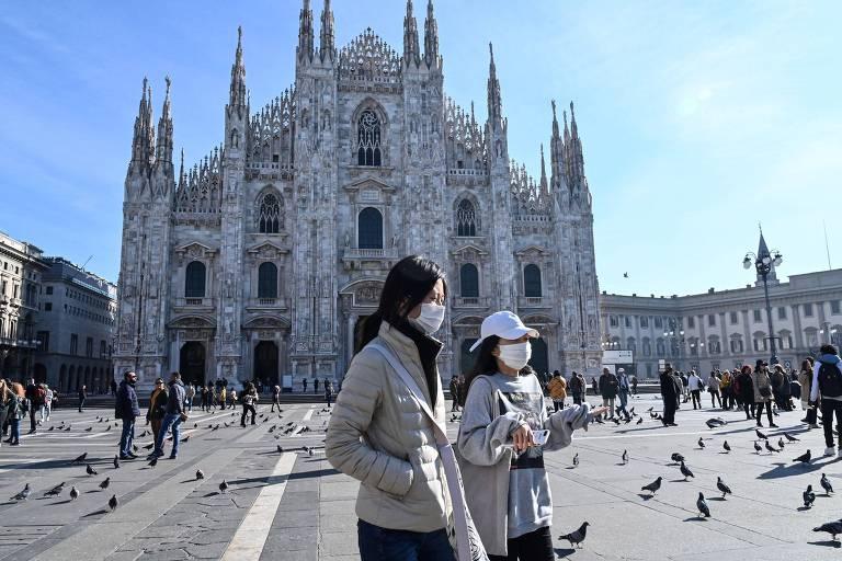 Mulheres usam máscara facial diante da catedral Duomo, fechada pelas autoridades