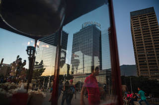 Offices for the food conglomerate Polar are seen through reflections in a window in Caracas, Venezuela, Feb. 8, 2020. (Adriana Loureiro Fernandez/The New York Times)