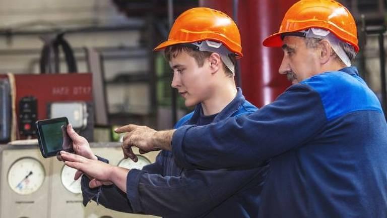 Dois homens de macacão azul e capacete laranja mexem em máquina