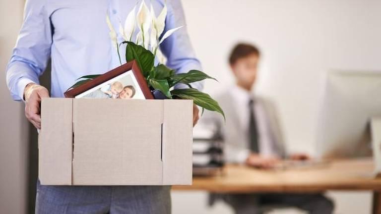 Homem carrega caixa com seus pertences do trabalho