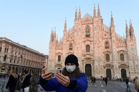 A woman wearing a protective facemask takes a selfie picture in the Piazza del Duomo in central Milan, on February 24, 2020, following security measures taken in northern Italy against the COVID-19 the novel coronavirus. - Italy reported on February 24, 2020, its fourth death from the new coronavirus, an 84-year old man in the northern Lombardy region, as the number of people contracting the virus continued to mount. (Photo by Miguel MEDINA / AFP)