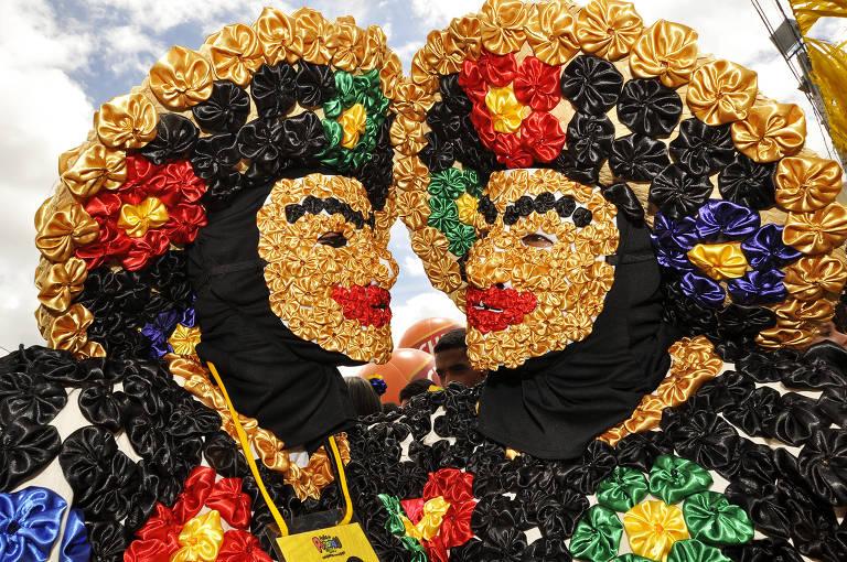 Casal de papangus, tradição da cidade de Bezerros, no agreste pernambucano, usam figurino recoberto de fuxicos para desfile no domingo de Carnaval