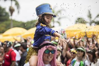 Carnaval em Sao Paulo . Crianca brinca no colo do pai durante passagem do bloco Vou de Taxi no Ibirapuera