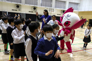 Students of Ariake-nishi Gakuen School wear protective face masks, following the outbreak of the coronavirus, as they wave to a para-athlete Chiaki Takada and Mascot Someity after an event Six Months to go until Tokyo 2020 Paralympic Games in Tokyo