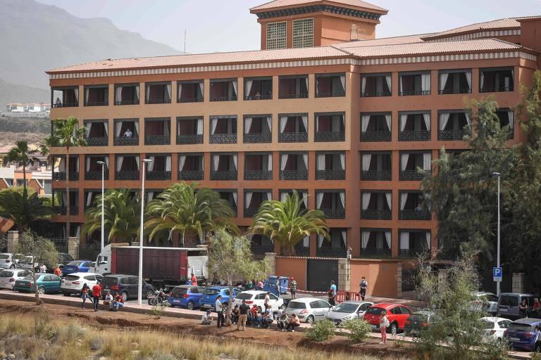 Fachada de hotel com carros estacionados em frente
