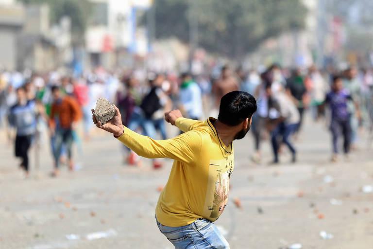 Homem que apóia lei da cidadania de Modi se prepara para jogar pedra em manifestantes que se opõem à medida em Nova Déli