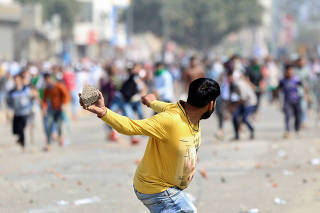A man supporting a new citizenship law throws a stone at those who are opposing the law, during a clash in New Delhi