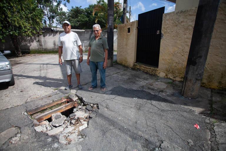 José Valdevino Ferreira (à esquerda) e seu vizinho Rubens Amancio afirmam que os buracos tomaram conta da rua Pássaro de Fogo, onde moram na Vila Ré (zona leste); moradores dizem reclamar em vão
