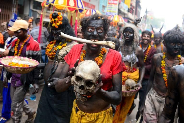 Homem pintado de preto morde osso enquanto segura crânio