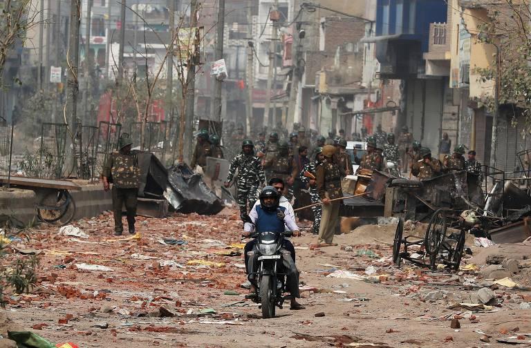 Forças de segurança em Nova Déli patrulham rua em área afetada pelos protestos a favor e contra a nova lei de cidadania na Índia
