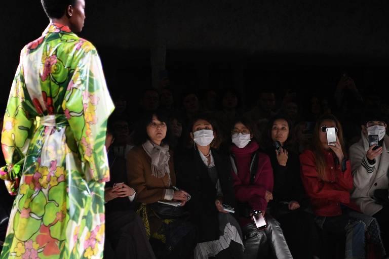 Modelo desfila peças do estilista Dries Van Noten e, ao fundo, convidados utilizam máscaras distribuídas pela organização do evento