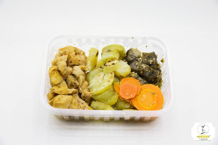 Marmita de plástico contendo frango em cubos, batata doce, berinjela picada e cenoura em rodelas