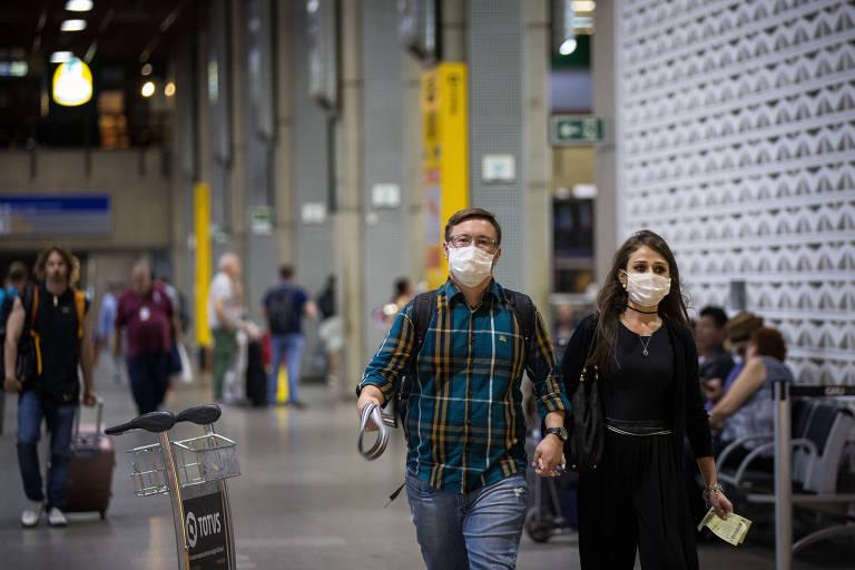Passageiros e funcionários usam máscaras de proteção no aeroporto Internacional de São Paulo, em Guarulhos